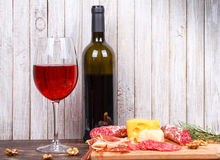 Glass and bottle of wine, cheese and prosciutto on wooden background Royalty Free Stock Photo