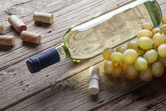 Glass bottle of wine with corkscrew on wooden table background Royalty Free Stock Photo