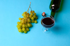 Glass, bottle of wine, green grapes on a blue background Stock Images