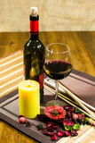 A glass and bottle of wine, lighted yellow candle, decorating flowers and leaves on a table Royalty Free Stock Images