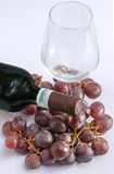 Glass, a bottle of wine and some grapes. A glass, a bottle of wine and some grapes royalty free stock images