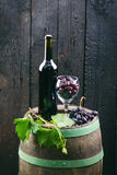 Glass and bottle of wine on a wooden barrel. Burnt, black wooden background. Vintage. Copyspace for a text. Grapes and green vine. Glass and bottle of wine on a stock images