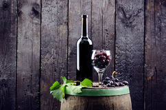 Glass and bottle of wine on a wooden barrel. Burnt, black wooden background. Vintage. Copyspace for a text. Grapes and green vine. Glass and bottle of wine on a stock photos