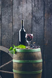 Glass and bottle of wine on a wooden barrel. Burnt, black wooden background. Vintage. Copyspace for a text. Grapes and green vine. Glass and bottle of wine on a stock image