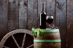 Glass and bottle of wine on a wooden barrel. Burnt, black wooden background. Vintage. Copyspace for a text. Grapes and green vine. Glass and bottle of wine on a royalty free stock images