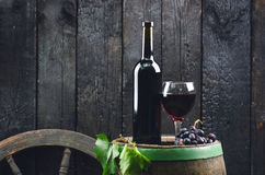 Glass and bottle of wine on a wooden barrel. Burnt, black wooden background. Vintage. Copyspace for a text. Grapes and green vine. Glass and bottle of wine on a stock photography