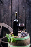 Glass and bottle of wine on a wooden barrel. Burnt, black wooden background. Vintage. Copyspace for a text. Grapes and green vine. Glass and bottle of wine on a royalty free stock photo