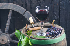 Glass and bottle of wine on a wooden barrel. Burnt, black wooden background. Vintage. Copyspace for a text. Grapes and green vine. Glass and bottle of wine on a royalty free stock photography