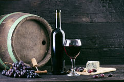 Glass and bottle of wine on a wooden barrel. Burnt, black wooden background. Vintage. Copyspace for a text. Grapes and green vine. Glass and bottle of wine on a royalty free stock image