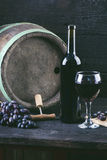 Glass and bottle of wine on a wooden barrel. Burnt, black wooden background. Vintage. Copyspace for a text. Grapes and green vine. Glass and bottle of wine on a royalty free stock photos