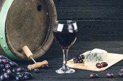 Glass and bottle of wine on a wooden barrel. Burnt, black wooden background. Vintage. Copyspace for a text. Grapes and green vine. Glass and bottle of wine on a stock photo