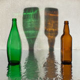 Glass bottles. Color shades on a wall from bottles Royalty Free Stock Images
