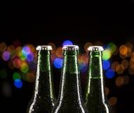 Glass bottles of beer on bar lights background Royalty Free Stock Image