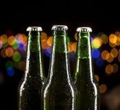 Glass bottles of beer on bar lights background Stock Image