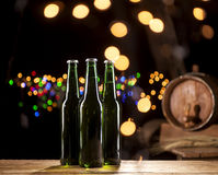 Glass bottles of beer and wooden barrel on bar lights background. Close up of three glass bottles of beer and wooden barrel on wooden table and bar lights Stock Photography
