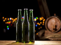 Glass bottles of beer and wooden barrel on bar lights background Royalty Free Stock Photography