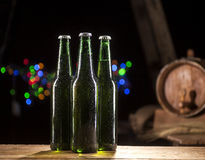 Glass bottles of beer and wooden barrel on bar lights background Royalty Free Stock Image