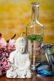 Glass bottles and buddha statue with flowers spa Stock Image