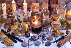 Glass bottles, candles, runes and magic objects on witch table. Occult, esoteric, divination and wicca concept. Alternative medicine and homeopathic vintage stock images