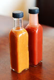 Glass bottles of chilli sauce Royalty Free Stock Image