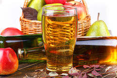 Glass and bottles of cider, fruits basket Stock Photos