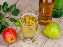 Glass and bottles of cider. On wooden background Royalty Free Stock Photos