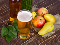 Glass and bottles of cider. On wooden background Royalty Free Stock Image