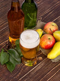 Glass and bottles of cider. On wooden background Royalty Free Stock Photography