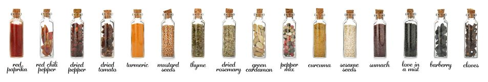 Glass bottles with different spices and herbs on white background. Large collection with names royalty free stock photography