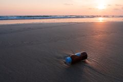 Glass bottles is dump into the sea, dirty waste on beach in summ Royalty Free Stock Photos