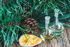 Glass bottles of essential oil with pine cones, oranges and fir branches on wooden background. Selective focus Stock Photos