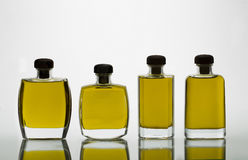 Glass bottles with extra virgin olive oil and intense yellow col. Group of Crystal Bottles transparent of different forms with oil Extra virgin olive of yellow Stock Photos