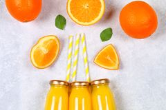 Glass bottles with fresh orange juice with orange slices and yellow tubes on a light gray table. Top view. Flat Lay. Glass bottles with fresh orange juice with stock photography
