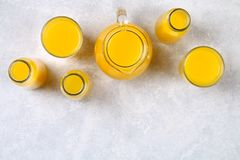 Glass bottles, glasses and a pitcher of fresh orange juice with slices of orange and yellow tubes on a light gray table. Top view. Flat Lay stock images