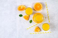 Glass bottles, glasses and a pitcher of fresh orange juice with slices of orange and yellow tubes on a light gray table. Top view. Flat Lay royalty free stock photography