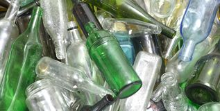Glass bottles inside a glass recycling. Container Royalty Free Stock Image
