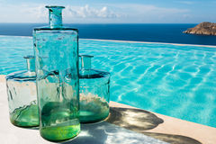 Glass bottles next to an infinity pool Royalty Free Stock Photo
