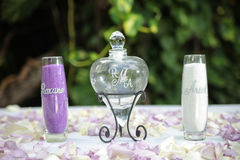 Glass bottles and petals. Glass bottles inscribed with names next to love heart bottle with stopper on table scattered with flower petals Royalty Free Stock Photo