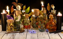 Glass bottles with potions and herbs and black candle on witch table Royalty Free Stock Image