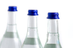 3 glass bottles in row filled with soda water with blue caps iso. Lated on white background royalty free stock photo
