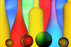 Glass bottles and spheres. On a multi-colored background Royalty Free Stock Photography