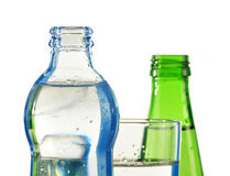 Glass and bottles of water isolated on white Stock Photography