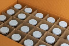 Glass bottles with white bottle caps in a cardboard box, Top vie stock images