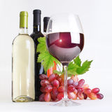 Glass, bottles of wine and grapes Stock Photos
