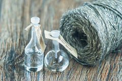 Glass bottles on a wooden surface with skein of jute twine. Selective focus Royalty Free Stock Image
