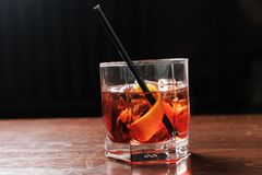 Glass of a Boulevardier cocktail with big ice cube and orange zest on the steel wooden bar counter on the blurred royalty free stock photography