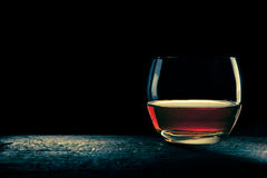 Glass of bourbon. Rounded glass of bourbon in shadows, minimal composition Stock Photos