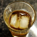 Whisky in a glass with ice and coke. A glass of bourbon whisky and coke over a bed of ice Stock Images