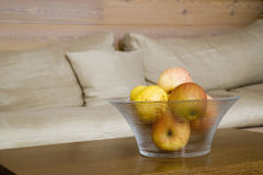 Glass bowl with apples on table in living room Stock Images