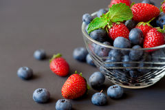 Glass bowl with assortment berries blueberries, strawberries and blackberries over black wooden table. Natural day light Royalty Free Stock Photos